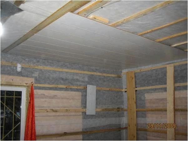Отделка белыми панелями потолка.